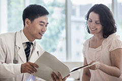 Doctor and patient sitting down and discussing medical record in the hospital Stock Images