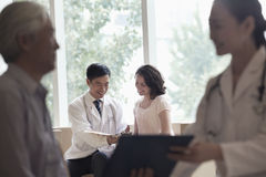 Doctor and patient sitting down and discussing medical record in the hospital, focus on background Stock Photo
