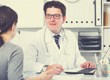 Doctor with patient sitting at the table. Portrait of young positive doctor with patient sitting at the table Royalty Free Stock Images