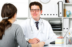 Doctor with patient sitting at the table. Portrait of young smiling doctor with patient sitting at the table Royalty Free Stock Photography