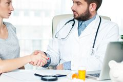 Smiling doctor shaking hands with a female patient in the office stock photography