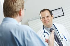 Doctor and patient talking. Medical office - smiling male doctor and patient talking Stock Photos