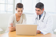 Doctor and patient using laptop in medical office Royalty Free Stock Image