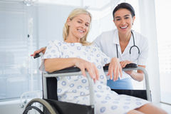 Doctor and patient in wheelchair smiling at camera. In hospital Stock Image