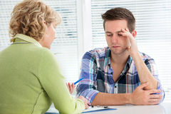 Doctor and patient. Young men visits doctors office suffering with depression Stock Images