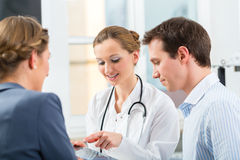 Doctor with patients in a consulting in clinic. Female doctor with her patients in clinic explaining something Stock Image