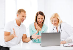 Doctor with patients looking at laptop Stock Photo