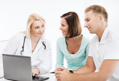 Doctor with patients looking at laptop Stock Photography