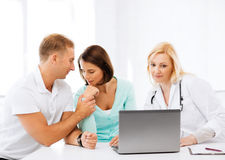 Doctor with patients looking at laptop Royalty Free Stock Photo