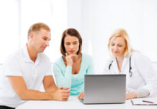 Doctor with patients looking at laptop Royalty Free Stock Photography