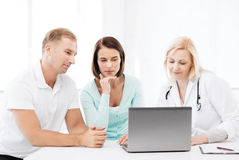 Doctor with patients looking at laptop Stock Image