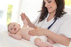 Pediatrician examining baby. Doctor pediatrician examining baby tummy in clinic royalty free stock photos