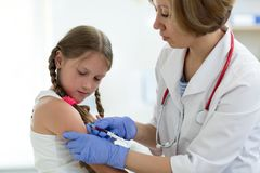 Doctor give injection to girl`s arm Royalty Free Stock Photos
