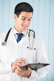 Doctor with pen and clipboard Royalty Free Stock Image