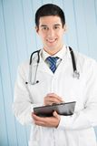 Doctor with pen and clipboard Stock Images