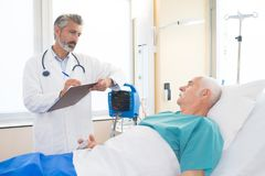 Doctor with pen and clipboard talking to patient. Doctor with a pen and clipboard talking to patient Royalty Free Stock Photography