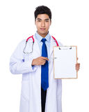 Doctor with pen point to clipboard Royalty Free Stock Image