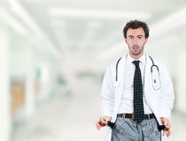 Doctor penniless showing empty pockets standing in hospital hallway. Stressed young doctor penniless showing empty pockets standing in hospital hallway clinic Stock Photography