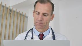 Doctor pensativo Thinking y trabajo en el ordenador portátil almacen de metraje de vídeo