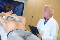 Doctor performing test on male patient. Man royalty free stock images