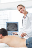 Doctor performing ultrasound scan on back of patient Stock Images