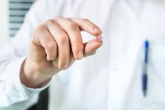 Doctor or pharmacist holding one pill between fingers. Medical professional and expert in white coat with medicine Stock Photo