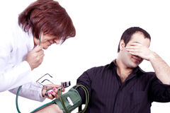 Doctor  phobia. A doctor measuring blood pressure of her patient, who has a phobia and in anxious  manner Royalty Free Stock Photography