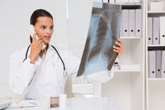 Doctor on the phone analysing xray results Stock Photography