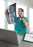 Doctor on Phone Discussing Patient's Spinal Scans royalty free stock photo