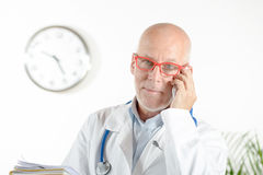 A doctor with phone in his office Royalty Free Stock Photo