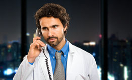 Doctor on the phone at late night in his studio Royalty Free Stock Photography