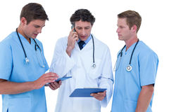 Doctor on the phone reading notes Stock Photo