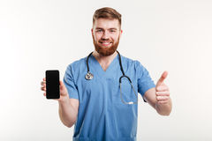 Doctor with phone showing thumb up. Male doctor showing thumb up and blank cellphone isolated over white background Royalty Free Stock Photo