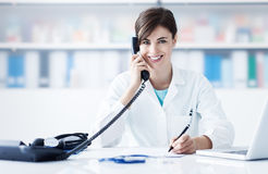 Doctor on the phone. Young female doctor working at office desk and answering phone calls stock photos