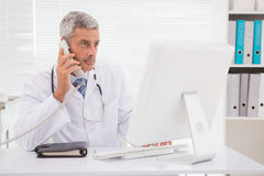 Doctor phoning and using computer Royalty Free Stock Images
