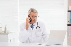 Doctor phoning and using computer Royalty Free Stock Photography