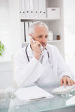 Doctor phoning and using computer Royalty Free Stock Image