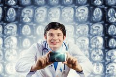 Doctor with photo camera. Young funny doctor taking photos with camera royalty free stock photo