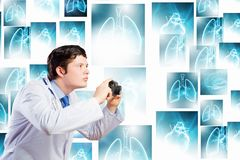Doctor with photo camera. Young funny doctor taking photos with camera stock photo