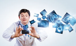 Doctor with photo camera. Young funny doctor taking photos with mobile phone camera stock photos