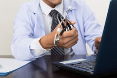 Doctor, physician holding stethoscope showing medical records on Royalty Free Stock Images