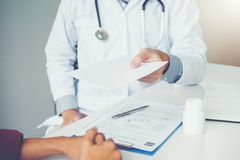 Doctor or physician writing diagnosis and giving a medical prescription to female Patient.  royalty free stock photography