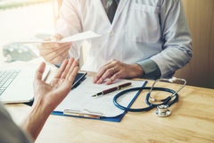 Doctor or physician writing diagnosis and giving a medical presc Stock Photography