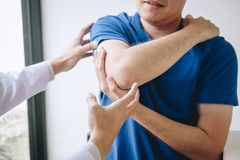 Doctor physiotherapist assisting a male patient while giving exercising treatment massaging the arm of patient in a physio room,. Rehabilitation physiotherapy stock images