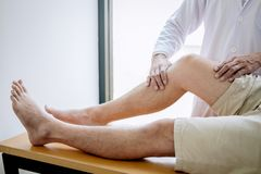 Doctor physiotherapist assisting a male patient while giving exercising treatment massaging the leg of patient in a physio room,. Rehabilitation physiotherapy stock image