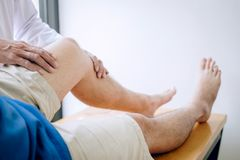 Doctor physiotherapist assisting a male patient while giving exercising treatment massaging the leg of patient in a physio room,. Rehabilitation physiotherapy stock images