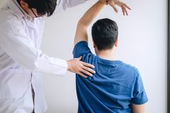 Doctor physiotherapist assisting a male patient while giving exercising treatment massaging the shoulder of patient in a physio. Room, rehabilitation royalty free stock photo