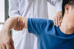 Doctor physiotherapist assisting a male patient while giving exercising treatment massaging the shoulder of patient in a physio. Room, rehabilitation royalty free stock photos