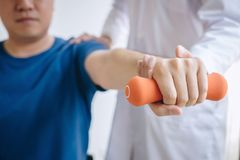 Doctor physiotherapist assisting a male patient while giving exercising treatment on stretching his arm with dumbbell in the. Clinic, Rehabilitation stock images