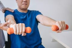 Doctor physiotherapist assisting a male patient while giving exercising treatment on stretching his arm with dumbbell in the. Clinic, Rehabilitation royalty free stock photos